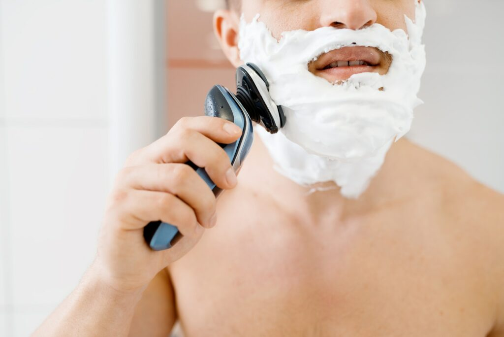 Man shaves his foamed beard with an electric razor